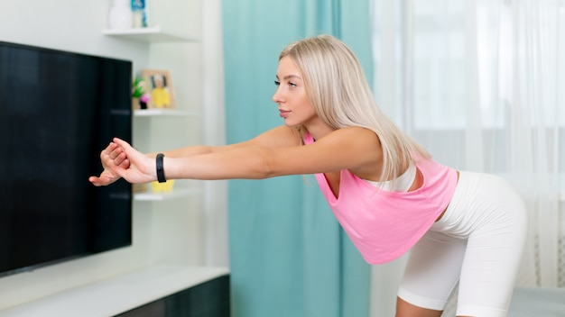 Mooie vrouw in mode sportieve kleding maken oefenen met gele band thuis. concept thuis workouts