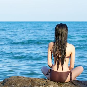 Mooie vrouw in natte bikini zittend op het strand op zomerdag