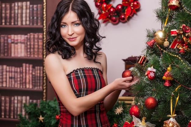 Mooie vrouw in nieuwjaar interieur jurken kerstboom