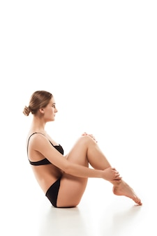 Mooie vrouw in ondergoed dat op witte vloer wordt geïsoleerd Gratis Foto