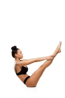 Mooie vrouw in ondergoed geïsoleerd op een witte muur. schoonheid, cosmetica, spa, ontharing, behandeling en fitness concept. fit en sportief, sensueel lichaam met verzorgde huid, oefeningen doen.