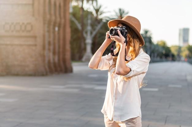 Mooie vrouw in ontdekkingsreiziger outfit reizen en fotograferen met vintage camera.