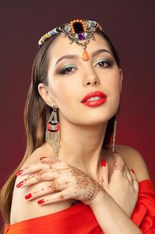 Mooie vrouw in oosterse stijl met mehendi op dark