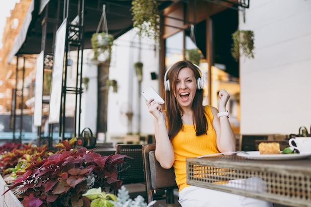 Mooie vrouw in openlucht straat coffeeshop café aan tafel zitten, muziek luisteren in koptelefoon, mobiele telefoon gebruiken, ontspannen in restaurant op vrije tijd