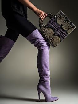 Mooie vrouw in paarse hoge laarzen. modieus meisje houdt stijlvolle violet lederen tas. glamour stijlvol concept. kunst. model loopt na het winkelen.