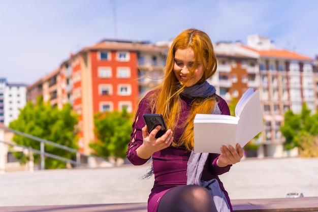 Mooie vrouw in paarse jurk en sjaal die een boek leest in een park in de stad, een bericht leest aan de telefoon