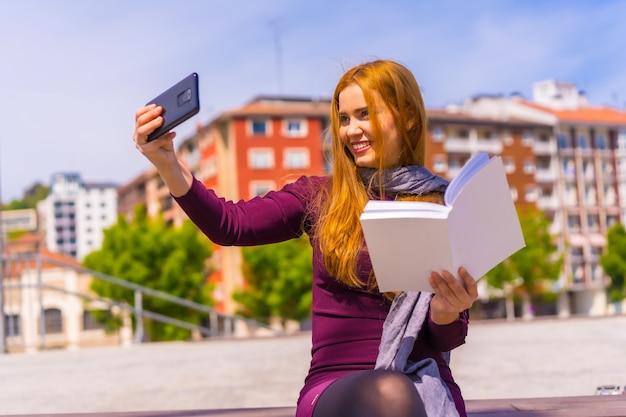Mooie vrouw in paarse jurk en sjaal die een boek leest in een park in de stad, een selfie neemt met de mobiele telefoon