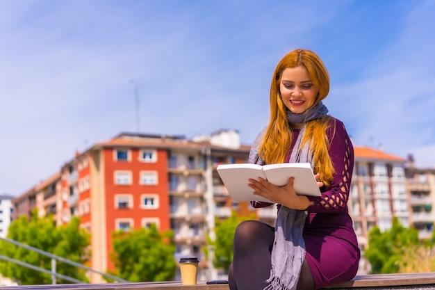 Mooie vrouw in paarse jurk en sjaal die een boek leest in een park in de stad, zich verbeeldt en geniet van lezen