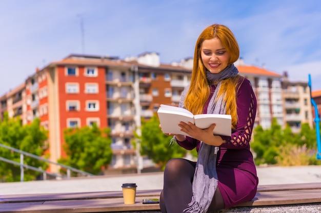 Mooie vrouw in paarse jurk en sjaal die een boek leest in een park in de stad