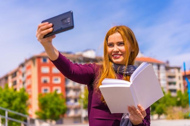 Mooie vrouw in paarse jurk en sjaal met een boek in haar hand in een park in de stad, een selfie maken met de mobiele telefoon