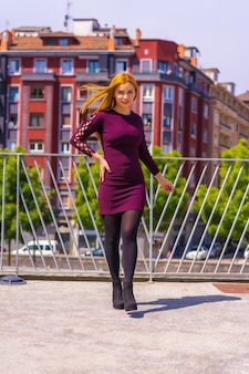 Mooie vrouw in paarse jurk en zwarte laarzen genieten in een park in de stad, poseren kijkend naar de camera