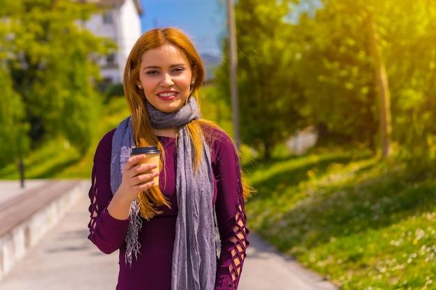 Mooie vrouw in paarse jurk en zwarte laarzen genietend in een park in de stad, poserend kijkend naar de camera, met een afhaalkoffie