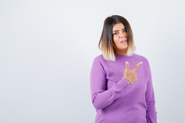 Mooie vrouw in paarse trui die naar de rechterbovenhoek wijst en besluiteloos kijkt, vooraanzicht.