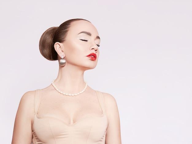 Mooie vrouw in parelhalsband en gouden oorringen.