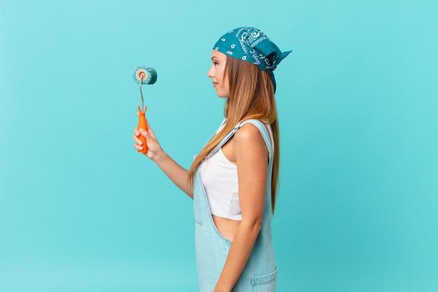 Mooie vrouw in profielweergave denken, fantaseren of dagdromen over het schilderen van een nieuwe huismuur