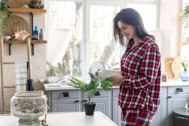 Mooie vrouw in pyjama het water geven installatie
