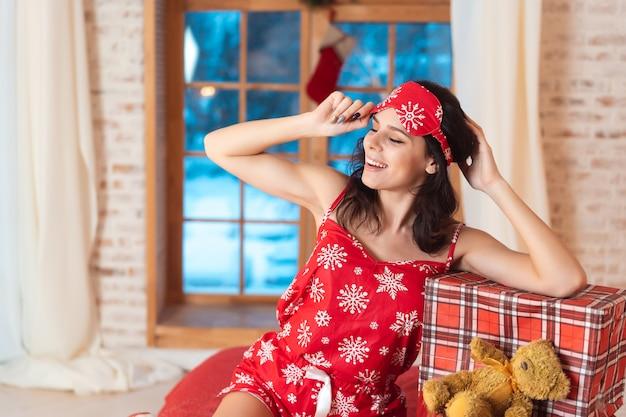 Mooie vrouw in pyjama met geschenkdoos