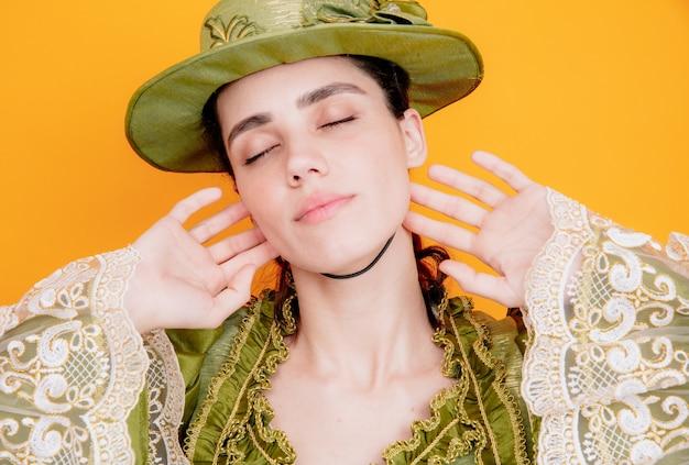 Mooie vrouw in renaissance jurk en hoed met ogen gesloten met dromerige uitdrukking op oranje