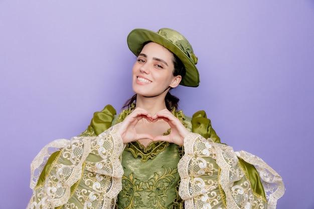 Mooie vrouw in renaissancejurk en hoed die vriendelijk lacht en een hartgebaar maakt met vingers blij en positief op blauw