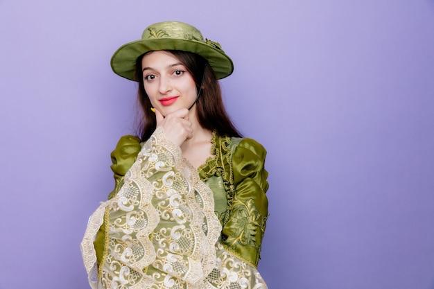 Mooie vrouw in renaissancejurk en hoed met peinzende uitdrukking die de hand op haar kin houdt en positief denkt over blauw