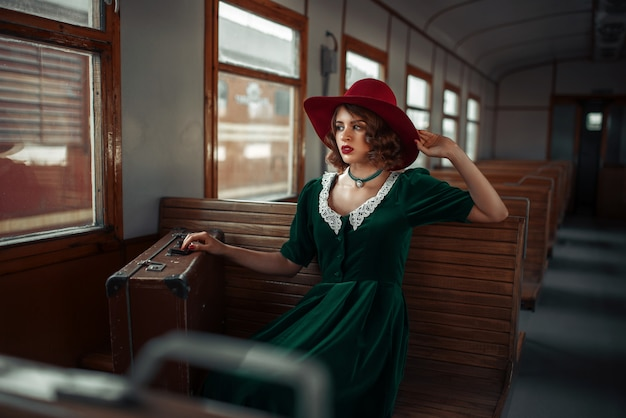 Mooie vrouw in retro trein, oud wagenbinnenland