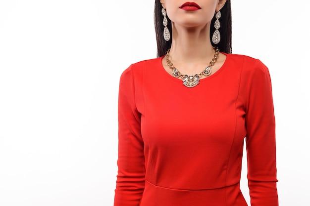 Mooie vrouw in rode avondjurk met ketting en oorbellen