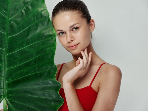 Mooie vrouw in rode badpak palmblad handgebaar charme