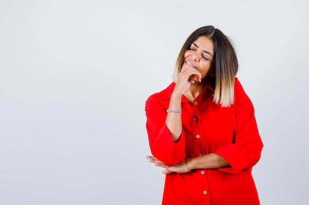 Mooie vrouw in rode blouse die de hand op de kin houdt, de ogen sluit en er vredig uitziet, vooraanzicht.
