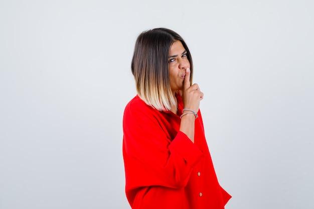 Mooie vrouw in rode blouse die stiltegebaar toont en er verstandig uitziet, vooraanzicht.