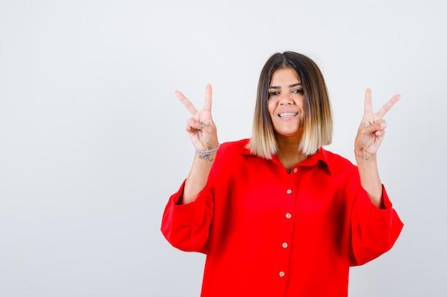 Mooie vrouw in rode blouse die vredesgebaar toont en vrolijk kijkt, vooraanzicht.