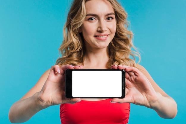 Mooie vrouw in rode bovenkant die mobiele telefoon toont