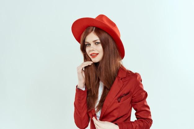 Mooie vrouw in rode hoed blazer make-up elegante stijl lichte muur.