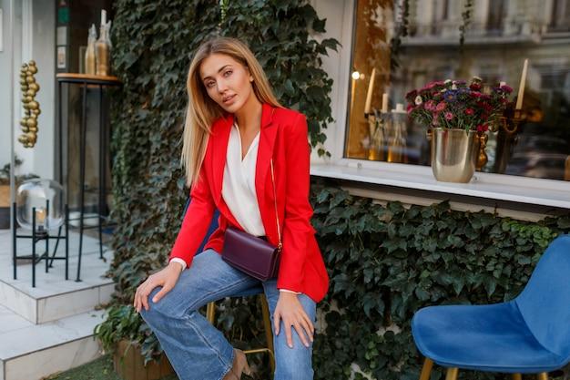 Mooie vrouw in rode jas rusten in straat café