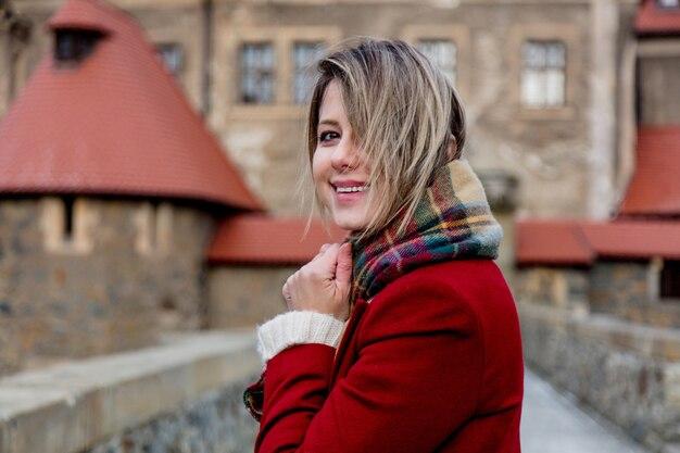 Mooie vrouw in rode jas verblijf in de buurt van kasteel in de winter. polen