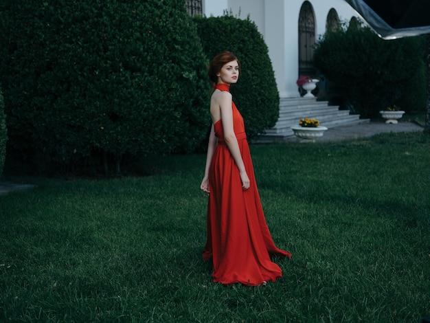 Mooie vrouw in rode jurk elegante stijl groene struiken in de tuin