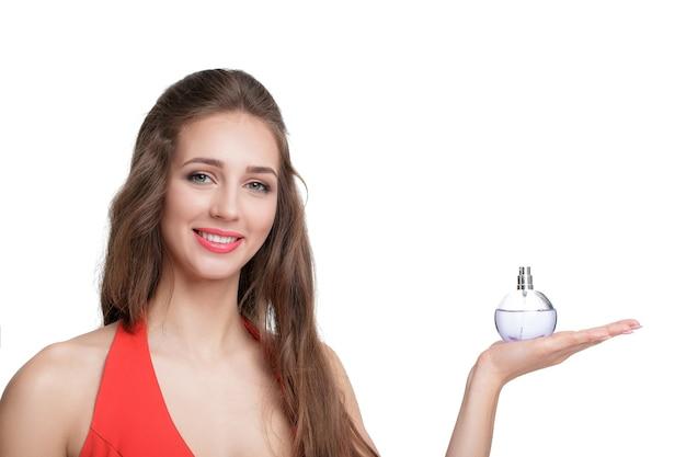 Mooie vrouw in rode jurk met fles parfum