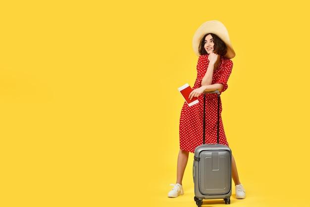 Mooie vrouw in rode jurk met grijze koffer en en paspoort gaan reizen op gele achtergrond. kopieer ruimte