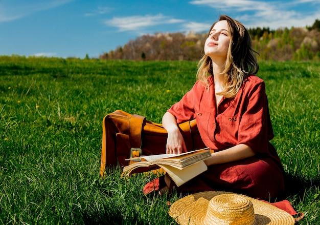 Mooie vrouw in rode jurk met koffer en boek zittend op de weide
