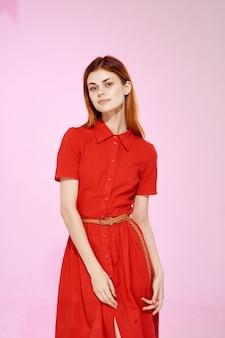 Mooie vrouw in rode jurk mode elegante stijl roze achtergrond