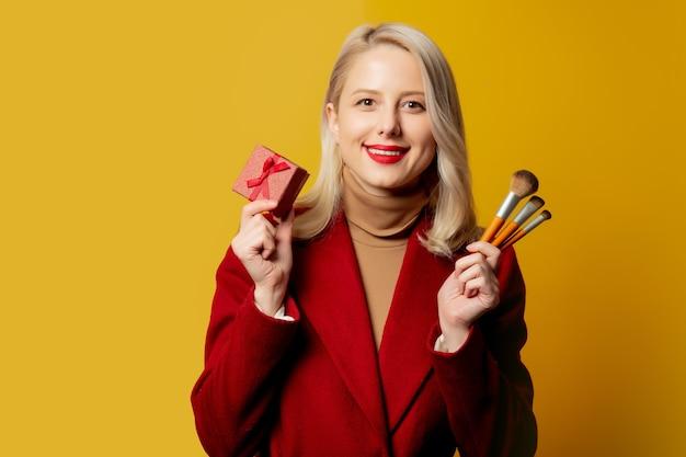 Mooie vrouw in rode laag met borstels en giftdoos op gele muur