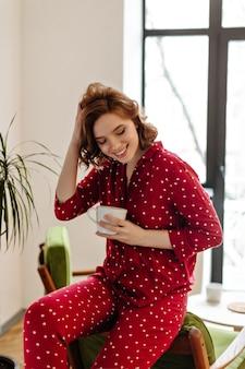 Mooie vrouw in rode pyjama zittend op een stoel en krullend haar aan te raken. binnen schot van lachende jonge vrouw met kopje koffie.