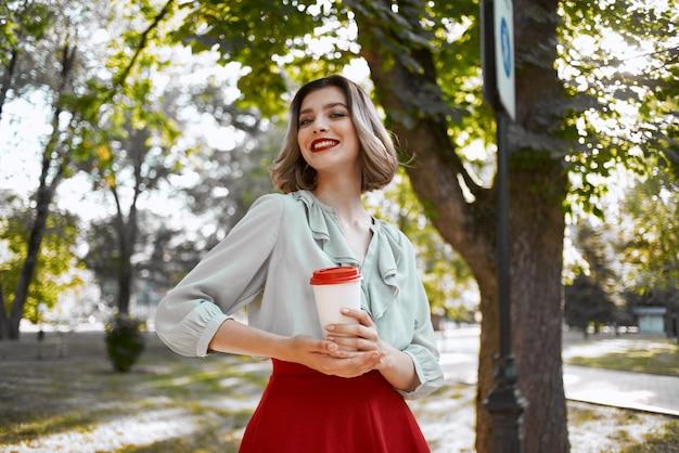 Mooie vrouw in rode rok een kopje koffie in de vrije tijd van de parkwandeling