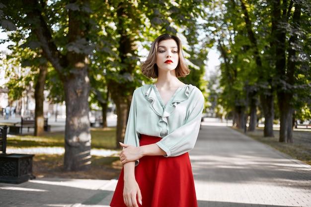 Mooie vrouw in rode rok in het park lopen levensstijl frisse lucht
