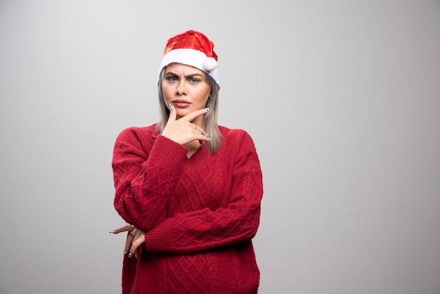 Mooie vrouw in rode trui die aan haar baan denkt.