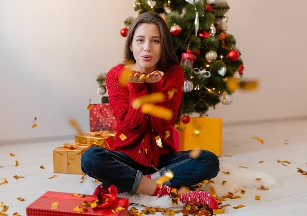 Mooie vrouw in rode trui om thuis te zitten op kerstboom gouden confetti gooien omringd met cadeautjes en geschenkdozen