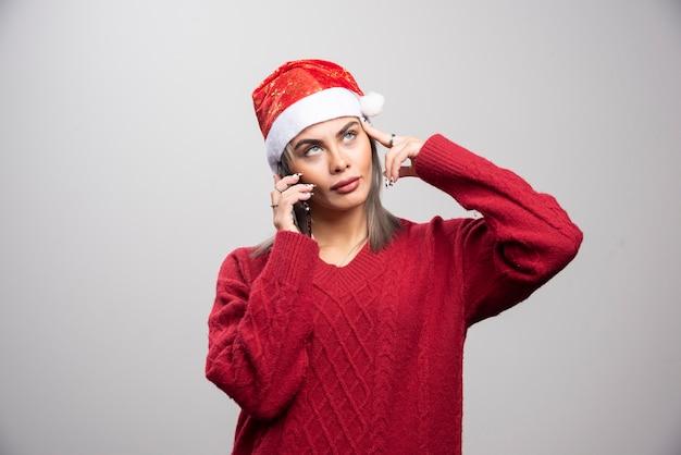 Mooie vrouw in rode trui praten op mobiele telefoon.