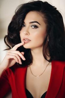 Mooie vrouw in rode verleidelijke ontroerende lippen met de hand.