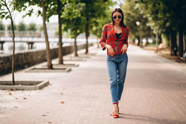 Mooie vrouw in rood jasje buiten in park