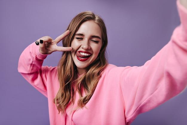 Mooie vrouw in roze hoodie glimlachend en selfie te nemen op paarse muur