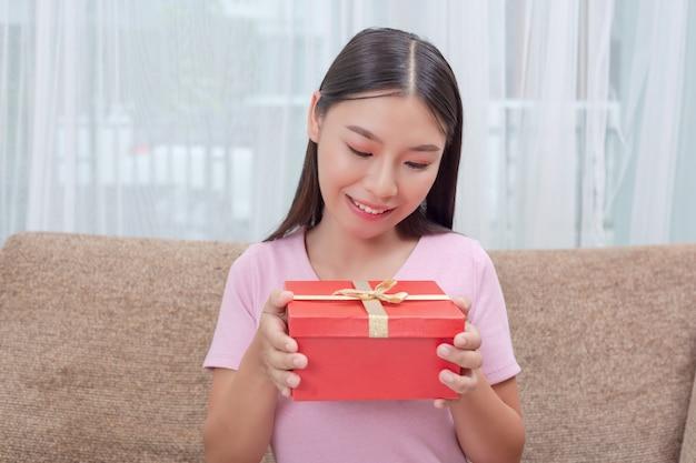 Mooie vrouw in roze jurk, zittend op de bank, het openen van een geschenkdoos.
